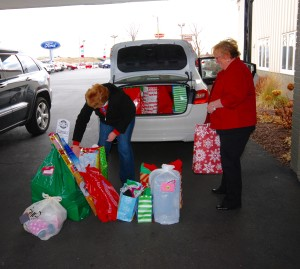 Car full of christmas presents with women and christmas presents in front of it